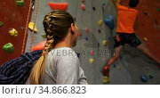 Woman watching a man climbing artificial wall 4k. Стоковое видео, агентство Wavebreak Media / Фотобанк Лори