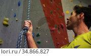 Man holding a rope near artificial wall 4k. Стоковое видео, агентство Wavebreak Media / Фотобанк Лори