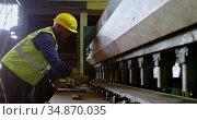 Male worker working on machine in warehouse 4k. Стоковое видео, агентство Wavebreak Media / Фотобанк Лори