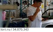 Male mechanic using mobile phone in garage 4k. Стоковое видео, агентство Wavebreak Media / Фотобанк Лори