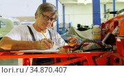 Male mechanic writing on clipboard 4k. Стоковое видео, агентство Wavebreak Media / Фотобанк Лори