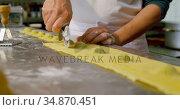 Male baker using pizza cutter on pasta dough in bakery shop 4k. Стоковое видео, агентство Wavebreak Media / Фотобанк Лори