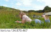 Woman writing on notepad in grass field 4k. Стоковое видео, агентство Wavebreak Media / Фотобанк Лори