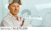 Mechanic looking at camera in garage 4k. Стоковое видео, агентство Wavebreak Media / Фотобанк Лори
