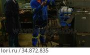 Two metalsmiths discussing over machine 4k. Стоковое видео, агентство Wavebreak Media / Фотобанк Лори