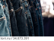 Jeans fabric background dark blue with copy space, a lot of clothes pants hanging are sold on the shop window. Стоковое фото, фотограф Светлана Евграфова / Фотобанк Лори