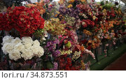 Colorful showcase of flower shop with large assortment of artificial flowers. Стоковое видео, видеограф Яков Филимонов / Фотобанк Лори