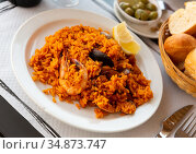 Delicious traditional Valencian seafood paella - savory rice dish with shrimps and clams. Стоковое фото, фотограф Яков Филимонов / Фотобанк Лори
