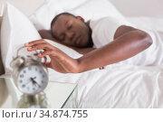 Sleepy man hitting his alarm clock in the morning. Стоковое фото, агентство Wavebreak Media / Фотобанк Лори