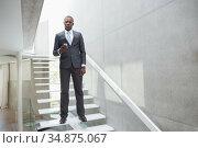 Stern businessman holding his smartphone. Стоковое фото, агентство Wavebreak Media / Фотобанк Лори