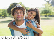 Hip young man giving a piggy back to his pretty girlfriend in the park. Стоковое фото, агентство Wavebreak Media / Фотобанк Лори