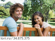 Happy young couple relaxing on park bench together. Стоковое фото, агентство Wavebreak Media / Фотобанк Лори