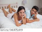 Unhappy couple lying on bed not talking. Стоковое фото, агентство Wavebreak Media / Фотобанк Лори