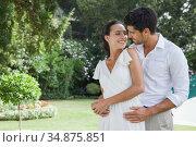 Happy couple standing in the garden embracing. Стоковое фото, агентство Wavebreak Media / Фотобанк Лори