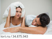 Irritated couple block ears with pillow because of loud snoring. Стоковое фото, агентство Wavebreak Media / Фотобанк Лори