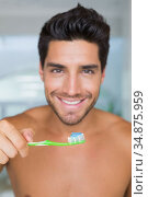 Shirtless man smiling with a green toothbrush in hand. Стоковое фото, агентство Wavebreak Media / Фотобанк Лори