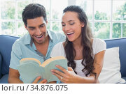 Couple laugh as they read book on the couch. Стоковое фото, агентство Wavebreak Media / Фотобанк Лори