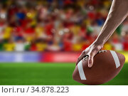 Composite image of man holding a american football ball . Стоковое фото, агентство Wavebreak Media / Фотобанк Лори