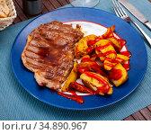Tasty beef steak with baked potatoes and ketchup. Стоковое фото, фотограф Яков Филимонов / Фотобанк Лори