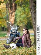 An adult woman a biker wearing black eyeglasses and leather brown jacket sitting under tree in autumn park next to her cruiser motorcycle. Стоковое фото, фотограф Кекяляйнен Андрей / Фотобанк Лори