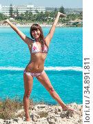 Happy and laughing woman wearing bikini standing on rock with hands up, the Mediterranean sea shore. Стоковое фото, фотограф Кекяляйнен Андрей / Фотобанк Лори