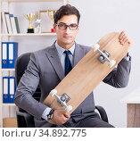 Young businessman riding skate in office during break. Стоковое фото, фотограф Elnur / Фотобанк Лори