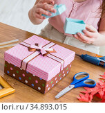 Woman decorating gift box for special occasion. Стоковое фото, фотограф Elnur / Фотобанк Лори