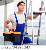 Young repairman climbing ladder at construction site. Стоковое фото, фотограф Elnur / Фотобанк Лори