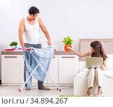 Man ironing, his lazy wife sitting. Стоковое фото, фотограф Elnur / Фотобанк Лори