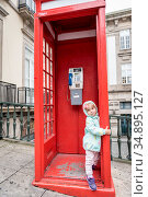 Little girl in a red phone booth. Стоковое фото, фотограф Сергей Фролов / Фотобанк Лори
