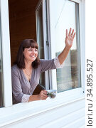 Adult woman waving hand and calling from the window in her home, holding a cup of tea or coffee. Стоковое фото, фотограф Кекяляйнен Андрей / Фотобанк Лори