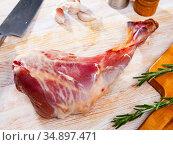 Refined goat leg with rosemary and garlic on cutting board. Стоковое фото, фотограф Яков Филимонов / Фотобанк Лори