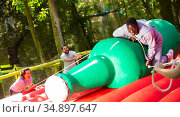 Attraction with a huge inflatable bottle - african-american man trying not to fall from her. Стоковое фото, фотограф Яков Филимонов / Фотобанк Лори