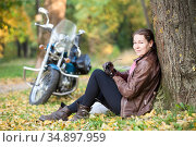 Pretty young woman in the autumn park, sitting next to motorcycle in a good mood, resting during her moto trip. Стоковое фото, фотограф Кекяляйнен Андрей / Фотобанк Лори