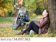 Chopper motorcycle standing on orange and yellow leaves while woman a rider resting under tree in autumn park. Стоковое фото, фотограф Кекяляйнен Андрей / Фотобанк Лори