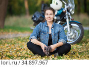 Attractive biker girl sits in the lotus position in front of stylish motorcycle at autumn park, smiling happy woman. Стоковое фото, фотограф Кекяляйнен Андрей / Фотобанк Лори