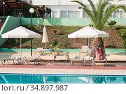 Hotel poolside with joyful woman lying under white parasol. Стоковое фото, фотограф Кекяляйнен Андрей / Фотобанк Лори