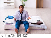 Young male employee working from home during pandemic. Стоковое фото, фотограф Elnur / Фотобанк Лори