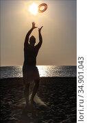 Young handsome guy throws a disc on a sandy beach. Стоковое фото, фотограф Юрий Бизгаймер / Фотобанк Лори