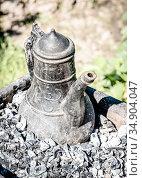 Old cast iron Turkish form kettle is heated on the coals. Стоковое фото, фотограф Сергей Фролов / Фотобанк Лори
