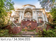 Abandoned dilapidated building in old park. Sweeping staircases, columns and a balustrade. Only the facade overgrown with forest remained. Example of mid-20th century architecture in the Soviet Union (2018 год). Стоковое фото, фотограф Сергей Фролов / Фотобанк Лори