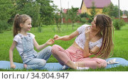 Young mother with dreadlocks hairstyle and little daughter are playing with each other while doing yoga exercises on grass in the park at the day time. Friendly family. Стоковое видео, видеограф Ольга Балынская / Фотобанк Лори
