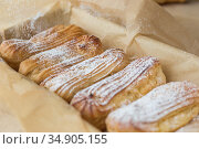 Freshly baked homemade eclairs on parchment paper. The process of sprinkling the pastries with powdered sugar. Стоковое фото, фотограф Galina Oleksenko / Фотобанк Лори