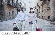 Traveling young spouses wearing medical masks to prevent viral infection strolling with luggage along city street on spring day. Стоковое видео, видеограф Яков Филимонов / Фотобанк Лори