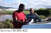 Afro and Latino men farmers signing papers near car on farm. Стоковое видео, видеограф Яков Филимонов / Фотобанк Лори