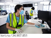 Woman wearing hi vis vest and face mask cleaning the office using disinfectant. Стоковое фото, агентство Wavebreak Media / Фотобанк Лори