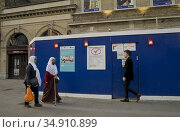 Local Muslim women walking by Whitechapel market ,with signs advising... Редакционное фото, фотограф Julio Etchart / age Fotostock / Фотобанк Лори