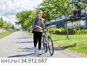 young man with bicycle walking along city street. Стоковое фото, фотограф Syda Productions / Фотобанк Лори