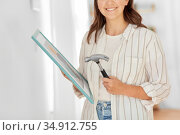 woman with hammer and picture in frame at home. Стоковое фото, фотограф Syda Productions / Фотобанк Лори