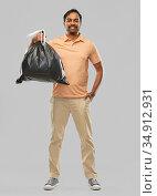 smiling indian man holding trash bag. Стоковое фото, фотограф Syda Productions / Фотобанк Лори